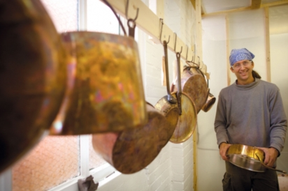Jim Hamann with a rack of copper pots ready to be refurbished